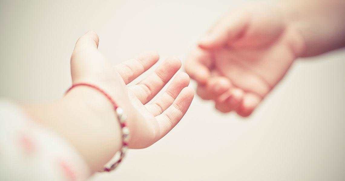 Händer som sträcks ut mot varandra
